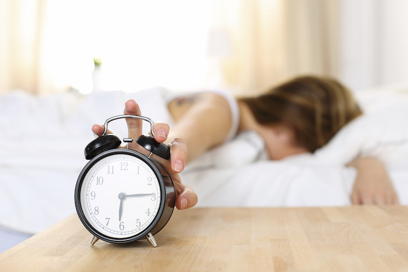 woman turning alarm clock off early morning